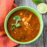Tortilla Soup with fresh lime and cilantro on Rustic Wood Background