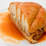Mexican Torta Ahogada, or drowned sandwich with pork on a white plate.